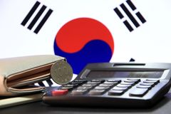 One hundred Korean won coin on reverse, KRW on black calculator with wallet on black floor and Korean flag background. The concept of finance stock photo