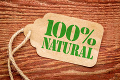 One hundred percent natural sign. A paper price tag against rustic red painted barn wood - shopping concept Stock Photo