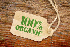 One hundred percent organic sign - a price tag. Against rustic red painted barn wood - shopping concept Royalty Free Stock Photography