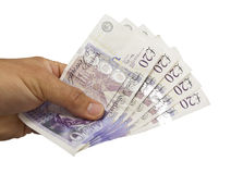 One Hundred Pounds Cash in Hand. Close-up of a hand holding one hundred pounds in twenty notes against a white background Stock Images