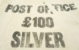 One hundred pounds sterling silver printed on a vintage money bag. One hundred pounds sterling / £100 silver printed on a vintage Post Office bank deposit royalty free stock photos