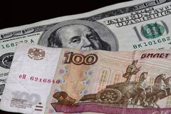 One hundred rubles banknote is above american dollars. On black background royalty free stock photos
