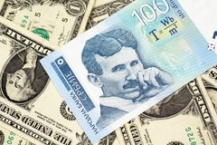 A one hundred Serbian dinar with American one dollar bills. A close up of a blue and white, one hundred Serbian dinar bank note on a background of American one stock photos