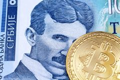 A one hundred Serbian dinar bank note with a gold physical Bitcoin. A close up image of a golden physical Bitcoin with a blue one hundred Serbian dinar bank note royalty free stock images