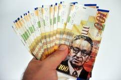 One Hundred Shekel Bills. A male hand holding One hundred shekel notes Royalty Free Stock Photography