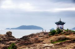 One Hundred Step Beach Putuoshan China. A gazebo and rocky shore at 100 step beach on the island of putuoshan china on an overcast day in Zhejiang province Stock Images