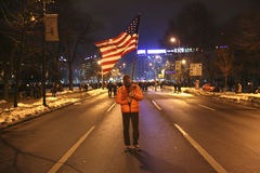 One hundred thousand protest as Romania relaxes corruption law. Bucharest, Romania - February 04, 2017:  Man waving american flag during the protest in front of Royalty Free Stock Image
