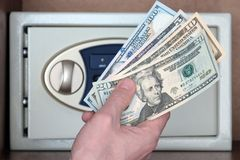 One hundred, twenty, ten and five dollars in a man`s hand against the background of a safe. The concept of storing money in royalty free stock image