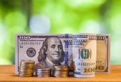 One hundred US dollar bills banknotes, with american cents coins. On green blurred bokeh background Royalty Free Stock Photography