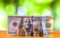 One hundred US dollar bills banknotes, with american cents coins. On green blurred bokeh background Stock Photo