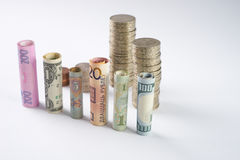 One hundred  US dollar and other currency rolled bills banknotes, with stacked coins Stock Photography