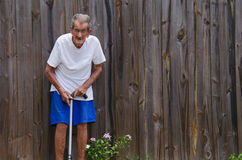 One hundred year very old centenarian senior man. A frail one hundred year old centenarian senior citizen man with a cane standing by flowers in front of a Stock Photos