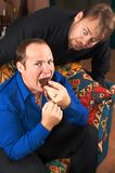 One hungry man staring. At the other one eating a huge chocolate muffin Royalty Free Stock Images