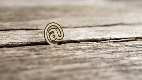 One At icon standing upright in a crack in rustic wood. Viewed low angle shallow dof with copy space Royalty Free Stock Photography