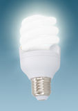 One Illuminated light bulb on blue background Royalty Free Stock Photo