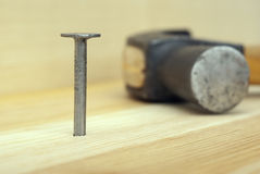 One iron nail and hammer. On wooden background Royalty Free Stock Photography