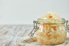 One jar of sauerkraut and carrots in its own juice with spices on a light, white wooden table, a horizontal kind of cabbage in a stock image
