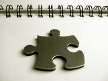 One jigsaw piece. Metallic jigsaw piece on a notebook stock photography