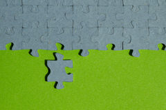 One jigsaw puzzle piece cut out on green background. With copy space Royalty Free Stock Image