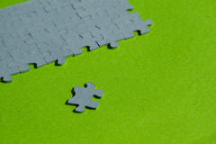 One jigsaw puzzle piece cut out on green background. With copy space Stock Photo