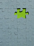 One jigsaw puzzle piece cut out on green background. With copy space Royalty Free Stock Photos
