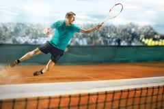 The one jumping player, caucasian fit man, playing tennis on the earthen court with spectators Stock Photography