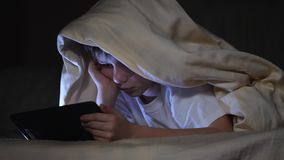 One kids using tablet pc under blanket at night. The boy plays computer games. One kids using tablet pc under blanket at night. The boy is playing computer games stock footage