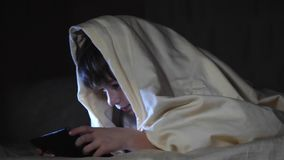 One kids using tablet pc under blanket at night. The boy plays computer games stock footage