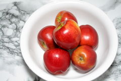 One kilo of red apples. Balanced in a white bowl to determine the amount Royalty Free Stock Photo