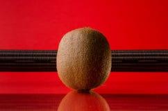 One kiwi fruit  on red background with stripe, horizontal shot. Picture presents one kiwi fruit  on red background with stripe, horizontal shot Royalty Free Stock Photos