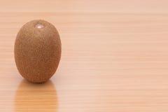 One kiwi fruit on the wooden table Royalty Free Stock Photos