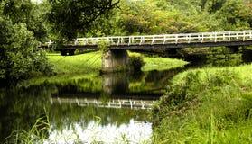 One Lane Bridge on Kauai. Narrow, one lane wooden bridge over river in Kauai, Hawaii.  White rustic wooden rails.  Reflection of bridge in water beneath bridge Stock Image