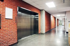 One large steel door elevator. One freight stainless steel door elevator surrounded by brcik wall of a deserted hallway. Could be office, school, retirement home Stock Photos