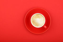 One latte cappuccino frothy coffee cup on red. One full morning latte cappuccino or macchiato coffee with milk froth in small red cup with saucer on red paper Royalty Free Stock Images