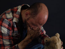 One Left Behind. A dirt covered man holds an orphaned dirty stuffed teddy bear in one hand, his jaw in another. Over a black background Royalty Free Stock Photo