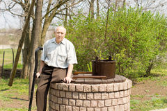 One legged man sitting on an old well Stock Photography