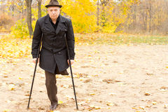 One-legged man walking with crutches in the park Stock Photos