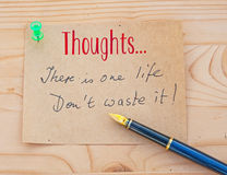 Only one life. Text Thoughts ... there is one life Don't waste it in handwritten script on a post-it style note pined to a wooden board Royalty Free Stock Images