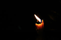 One light candle burning brightly, image is isolated against a b Royalty Free Stock Photography
