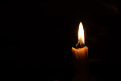 One light candle burning brightly, image is isolated against a b Stock Photo