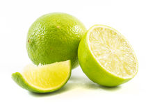 One lime, another cut in half and a small piece on a white background Stock Image