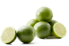 One lime and a half in front of others. On white background royalty free stock image