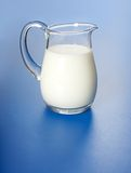 One liter milk. In glass jug, on blue surface Stock Images