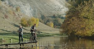 One littel boy with two guys fishing on a lake at nature. stock footage