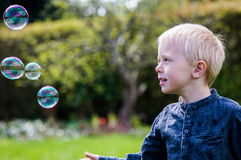 One Little boy blows soap bubbles in the garden on a summer day Stock Image