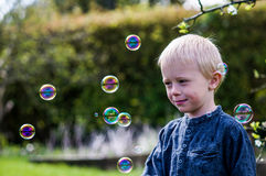 One Little boy blows soap bubbles in the garden on a summer day Royalty Free Stock Photo