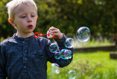 One Little boy blows soap bubbles in the garden on a summer day Stock Photos