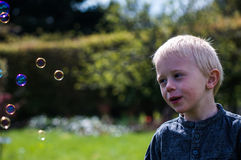 One Little boy blows soap bubbles in the garden on a summer day Stock Images