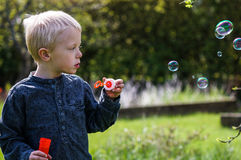 One Little boy blows soap bubbles in the garden on a summer day Royalty Free Stock Images