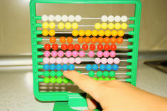 One little child learns math on abacus Stock Photo